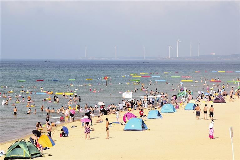 游客及市民在环海路沿线滨海旅游公园亲海戏水,消暑纳凉.